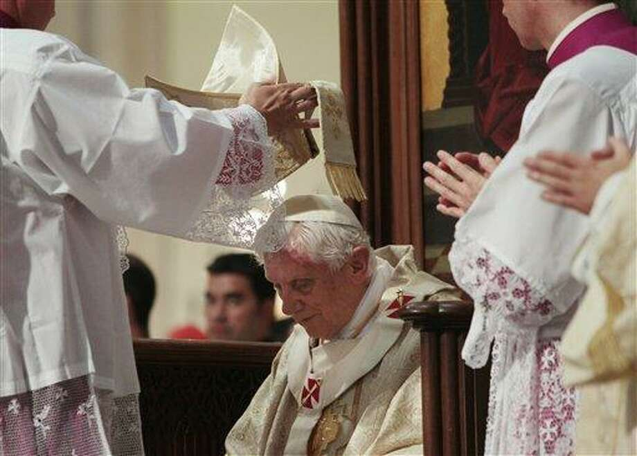 Pope Benedict XVI, center, his helped by a prelate with his miter during a mass inside St. Maria la Real de la Almudena Cathedral during the Catholic Church's World Youth Day celebrations, in Madrid, Saturday, Aug. 20, 2011. (AP Photo/Gregorio Borgia) Photo: AP / AP