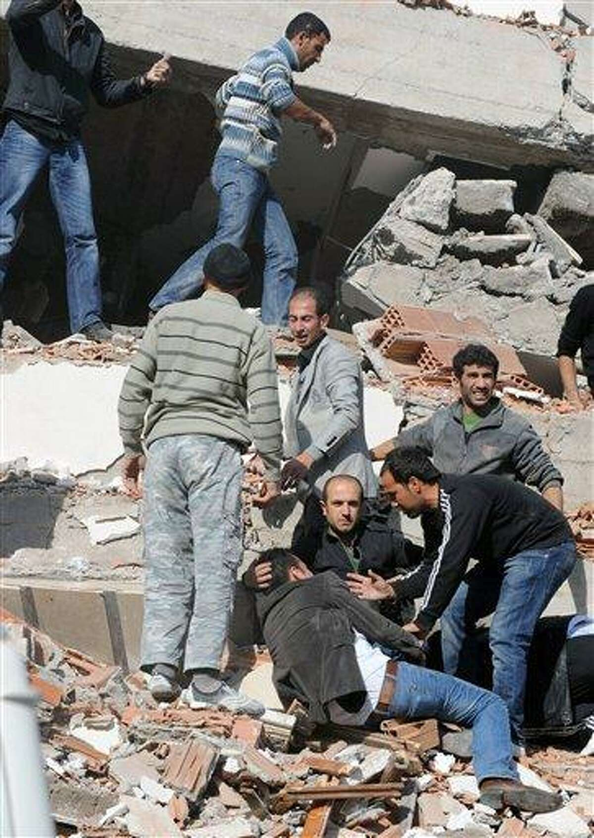 People try to save people trapped under debris in Tabanli village near the city of Van after a powerful earthquake struck eastern Turkey Sunday Oct. 23, 2011, collapsing some buildings and causing a number of deaths, an official said. ( AP Photo/ Abdurrahman Antakyali, Aatolia)