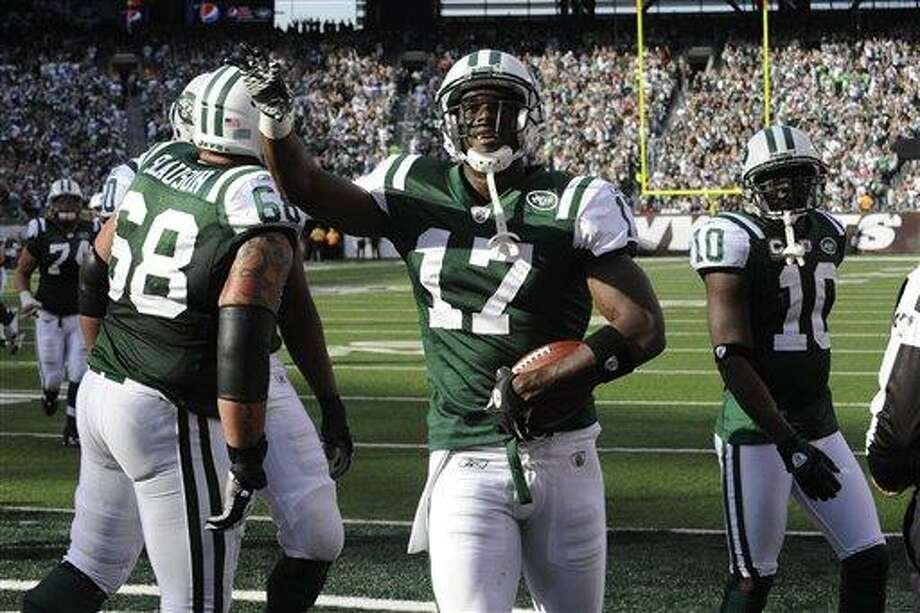 New York Jets' Plaxico Burress greets the crowd after scoring a touchdown during the third quarter of an NFL football game between the San Diego Chargers and the New York Jets, Sunday, Oct. 23, 2011, in East Rutherford, N.J. (AP Photo/Bill Kostroun) Photo: AP / FR51951 AP