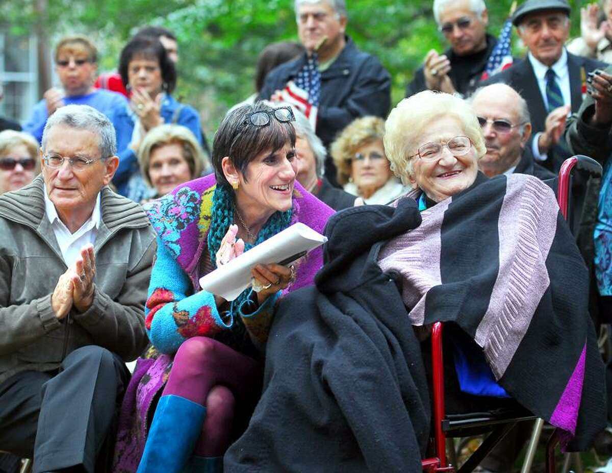 From left, Stanley Greenberg, his wife, U.S. Rep. Rosa DeLauro, and mother-in-law, Luisa DeLauro, listen to speakers during the dedication of the DeLauro Family Table at Wooster Square Park in New Haven Sunday. Photo by Arnold Gold/New Haven Register