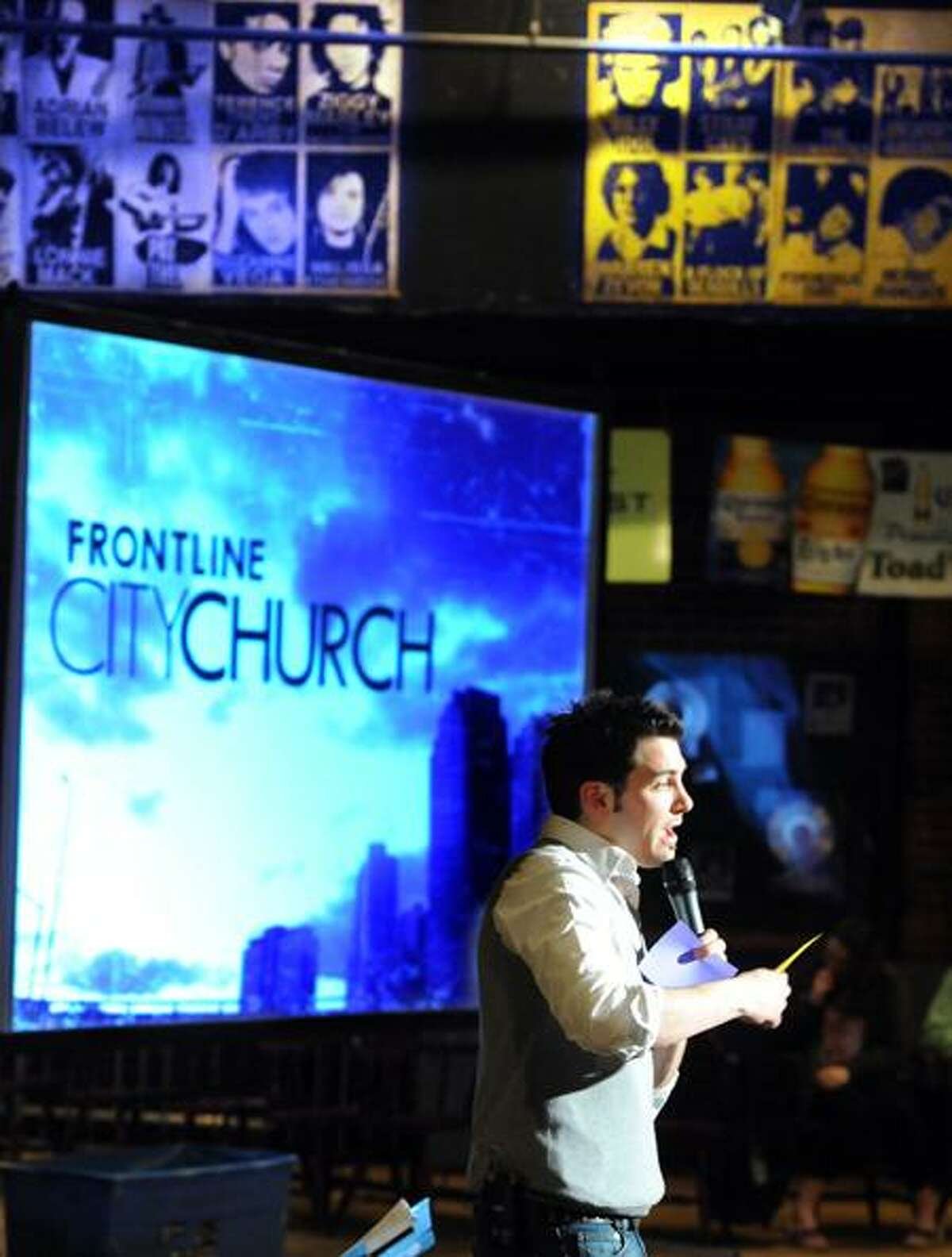 The inaugural gathering of the Frontline City Church at Toad's Place in New Haven on Easter. Lead Pastor Jason Kendrick of New Haven preaches under the watchful poster gazes of some of the performers who have played Toad's. Photo by Mara Lavitt/New Haven Register4/24/11