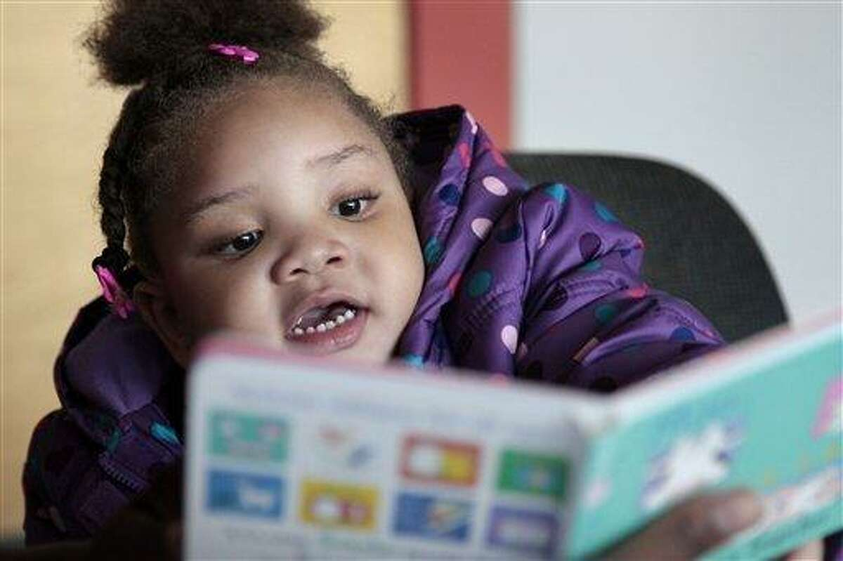 In this photo taken Dec. 8, 2011, Taliyah Garrett, 3, looks at a book as she gets help in learning to read by a coordinator from the Parent Child Home Program during a visit in Seattle. The home visiting program, supported by United Way of King County, Wash., helps children from low-income families prepare for kindergarten by tutoring parents in how to teach their children. Many of the nation's nonprofit organizations are digging in for another three to four years of financial distress, according to researchers who keep an eye on the charitable world. Associated Press