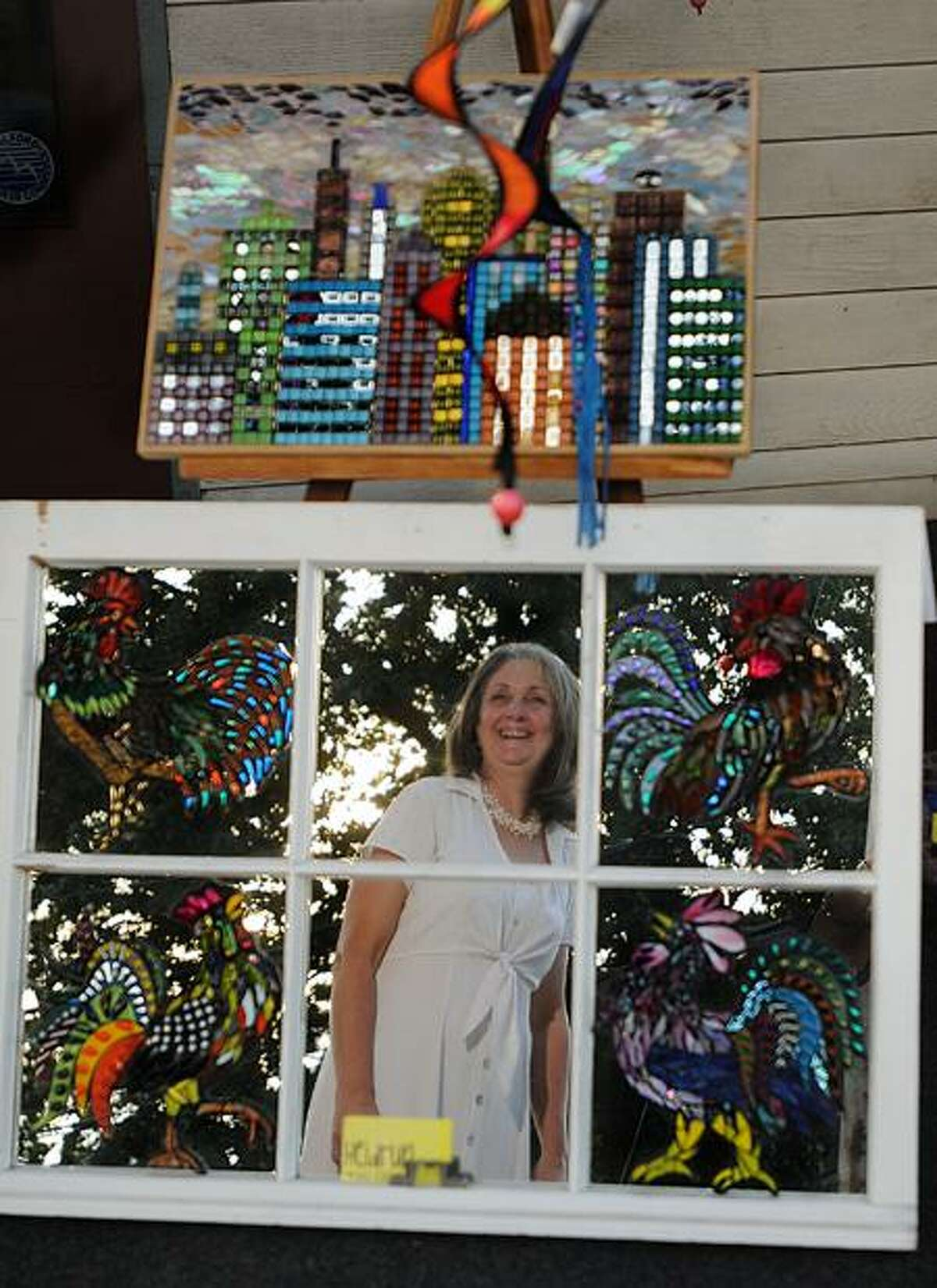 """Louise Herbert is reflected in """"Kikrtiki"""" created by artist Heidrun Morgan. The piece, diplayed at Canvas Patch, is part of the Open Doors and Windows Art Walk in downtown Milford. The annual event is sponsored by the Downtown Milford Business Association. Melanie Stengel/Register"""
