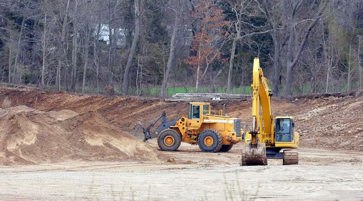 Ken Evarts runs a pay-loader at the site along Dairy Hill Road. (Peter Casolino/New Haven Register)