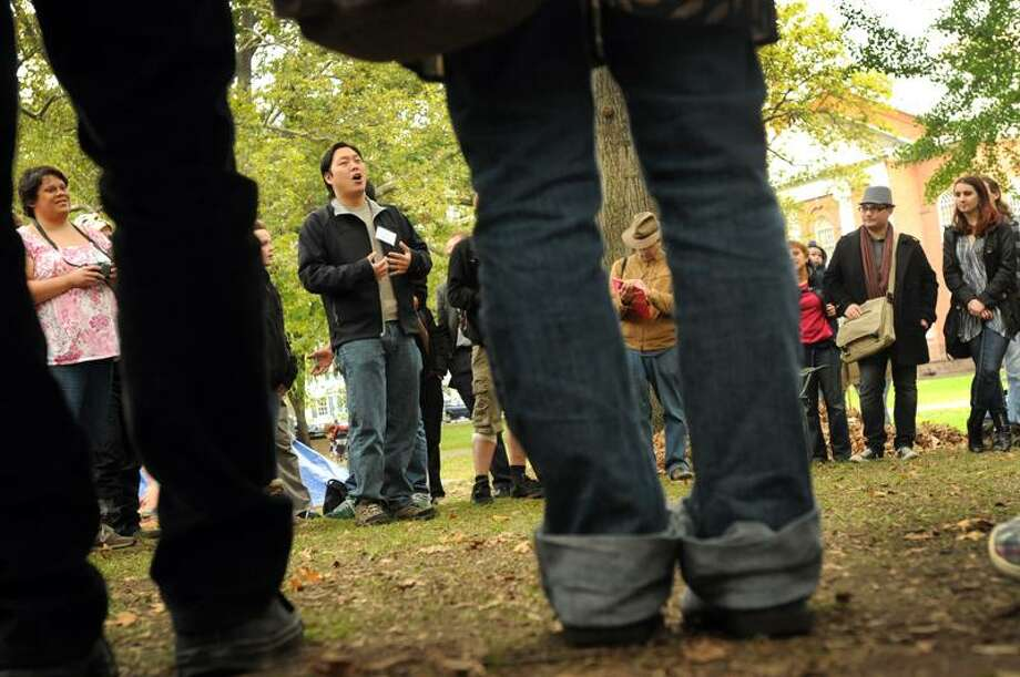 Jennifer Lopez of New Haven, left, and Andrew Jeon of New Haven of  the Occupy New Haven Media Group Committee, second from left, participate in the Occupy New Haven general assembly meeting Sunday afternoon  on the Upper Green.  The assemblies are when Occupy New Haven activists air proposals and vote on them.  Photo by Peter Hvizdak / New Haven Register / PETER HVIZDAK