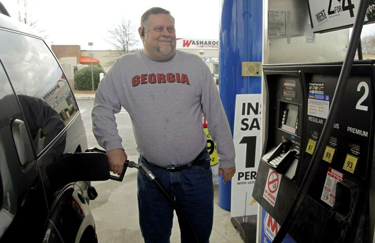 Michael Reed fills his gas tank at a station in Charlotte, N.C. The retail price of gasoline averaged more than $3.50 per gallon for the year, a record. The typical American household will have spent $4,155 filling up this year. (Associated Press)