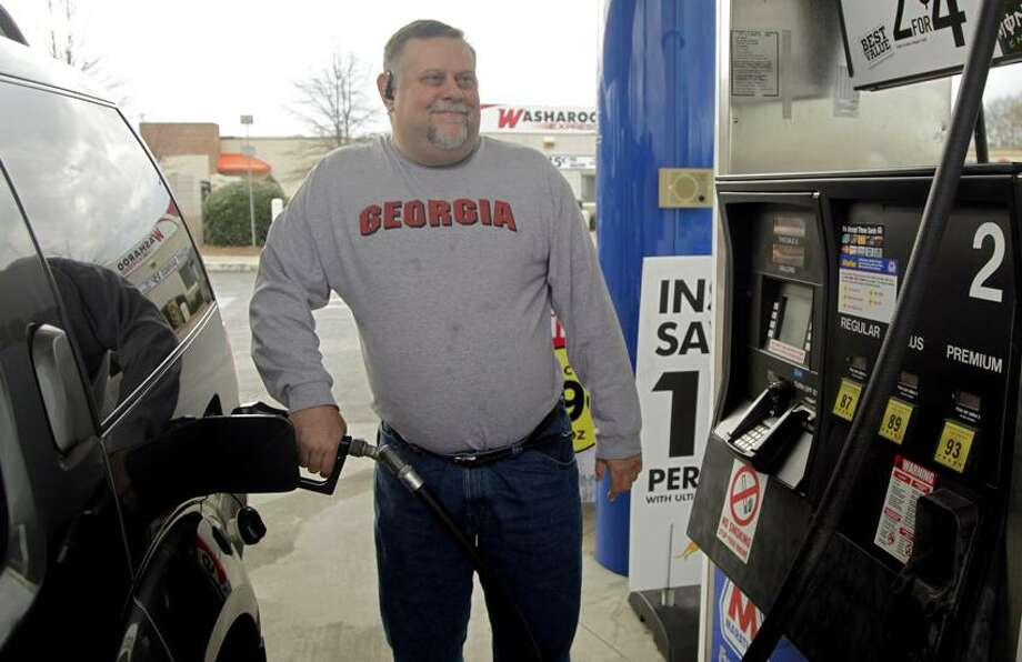Michael Reed fills his gas tank at a station in Charlotte, N.C. The retail price of gasoline averaged more than $3.50 per gallon for the year, a record. The typical American household will have spent $4,155 filling up this year. (Associated Press) Photo: AP / AP2011