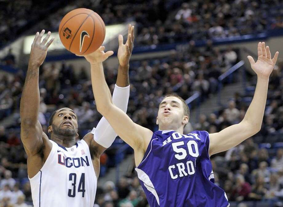 Connecticut's Alex Oriakhi (34) fights for a rebound with Holy Cross' Dave Dudzinski (50) during the first half of an NCAA college basketball game in Hartford, Conn., on Sunday, Dec. 18, 2011. (AP Photo/Fred Beckham) Photo: AP / AP2011