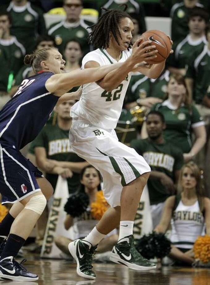 Connecticut's Heather Buck attempts to knock the ball away from Baylor center Brittney Griner in the first half of an NCAA college basketball game Sunday, Dec. 18, 2011, in Waco, Texas. (AP Photo/Tony Gutierrez) Photo: AP / AP2011