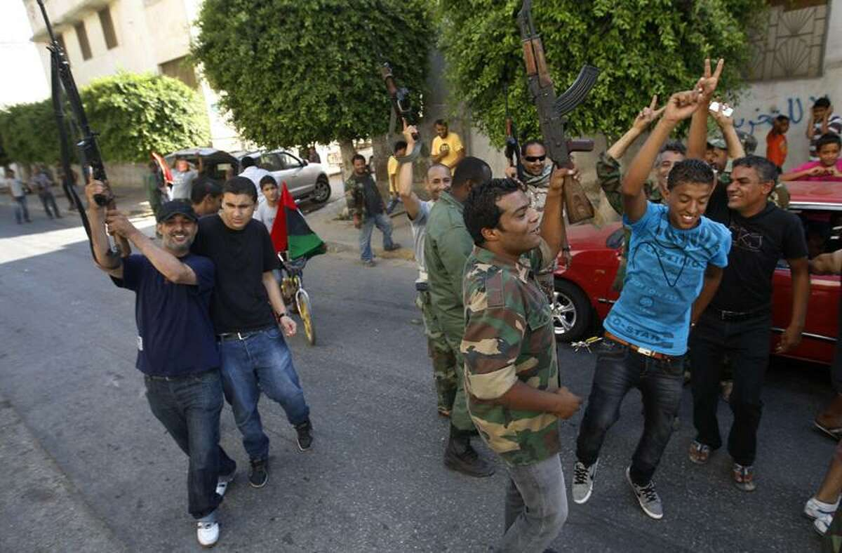 Libyan rebels open fire in Benghazi, Libya, in celebration Monday after hearing that the International Criminal Court has issued arrest warrants for Libyan leader Col. Moammar Gadhafi for crimes against humanity.(Associated Press)