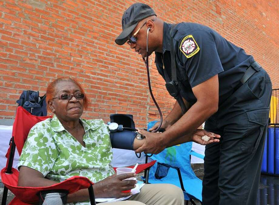 New Haven Fire Service paramedic Leon Brown takes Mary Hampton's blood pressure at Saturday's event. Brad Horrigan/Register
