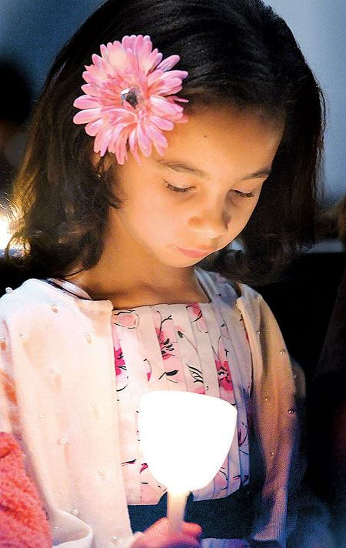 Nora Mullins, 7, of West Haven, holds her candle during an Easter vigil Saturday at the Church of the Holy Spirit in West Haven. (Melanie Stengel/Register)