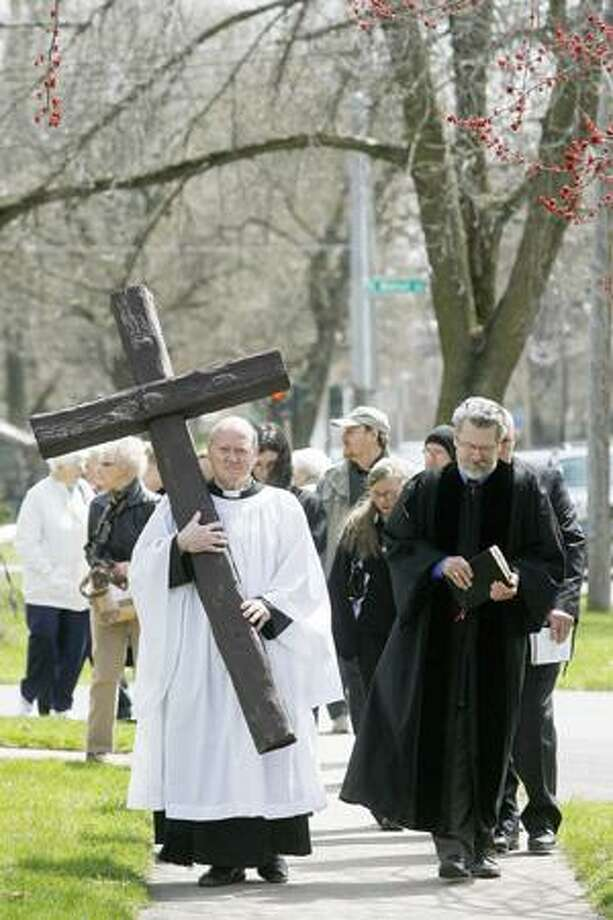 Dispatch Staff Photo by JOHN HAEGER Rev. James Heidt of St. John's Episcopal Church carries the cross as they make their way along Main Street in the City of Oneida as part of the Oneida Area Christian Churches Good Friday Service on Friday, April 22, 2011.