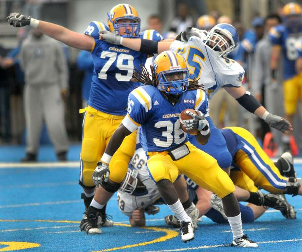 Running back Anthony Tillman of the University of New Haven runs for a long gain with the help of teammate ffensive tackle Lance Chapman, rear left, as he blocks R.J. Barden of Bentley College during first quarter football action Saturday 10/22/11 at the University of New Haven. Photo by Peter Hvizdak / NewHaven RegisterOctober 22, 2011 ph2391 Connecticut