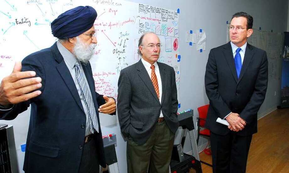 Gov. Dannel P. Malloy, right, speaks with Sukh Grewal, left, chief operating officer and founder of Grey Wall Software, and a lawyer for the company during a recent visit to Gray Wall's office in New Haven. Arnold Gold/Register