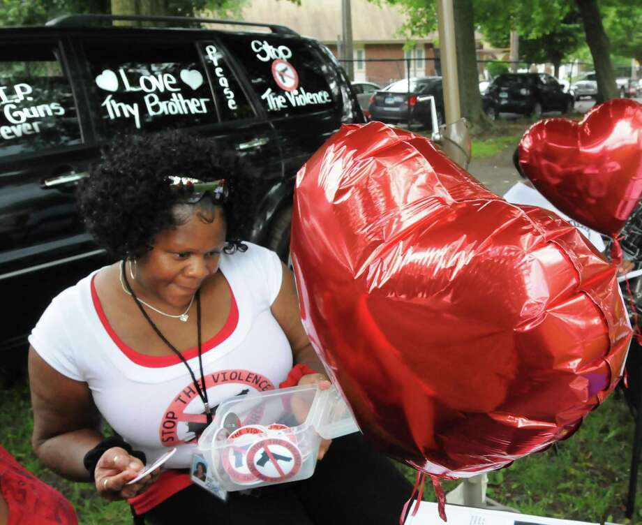 """Delisa Carney, of """"Stop the Violence,"""" looks over buttons to be given out at a peace gathering at Geoff Street Park held by the Freddie Fixer parade committee. Melanie Stengel/Register"""