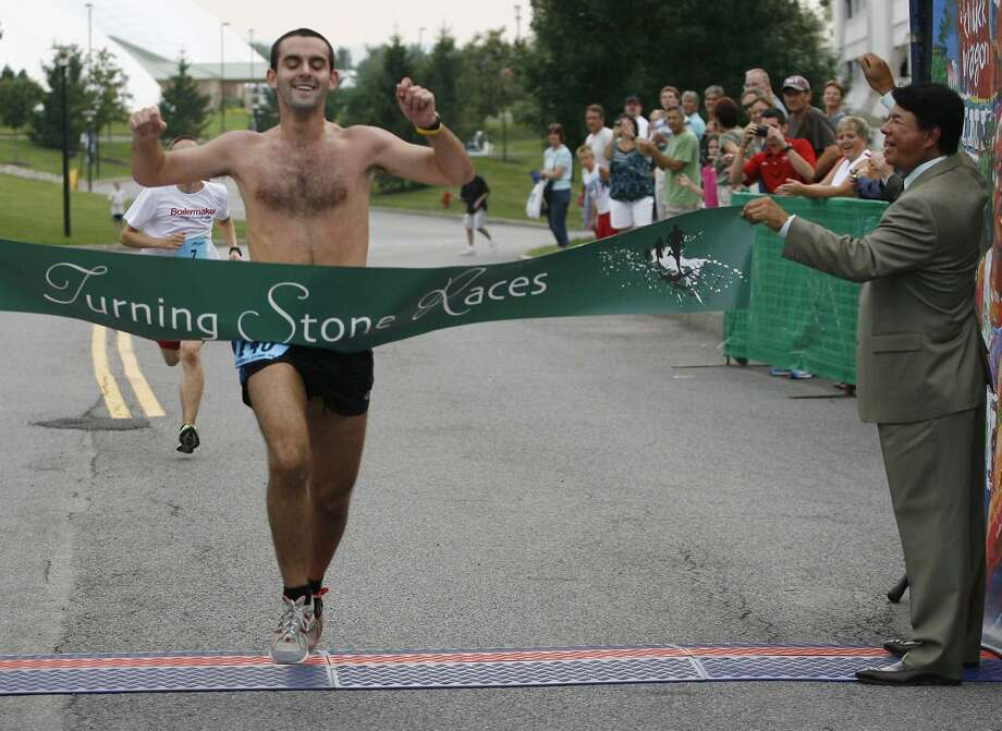 "Dispatch Staff Photo by JOHN HAEGER<a href=""http://twitter.com/oneidaphoto"">twitter.com/oneidaphoto</a>Steven Spittler crosses the finish line to win the inaugural 5K race at Turning Stone on Friday, Aug. 19, 2011."