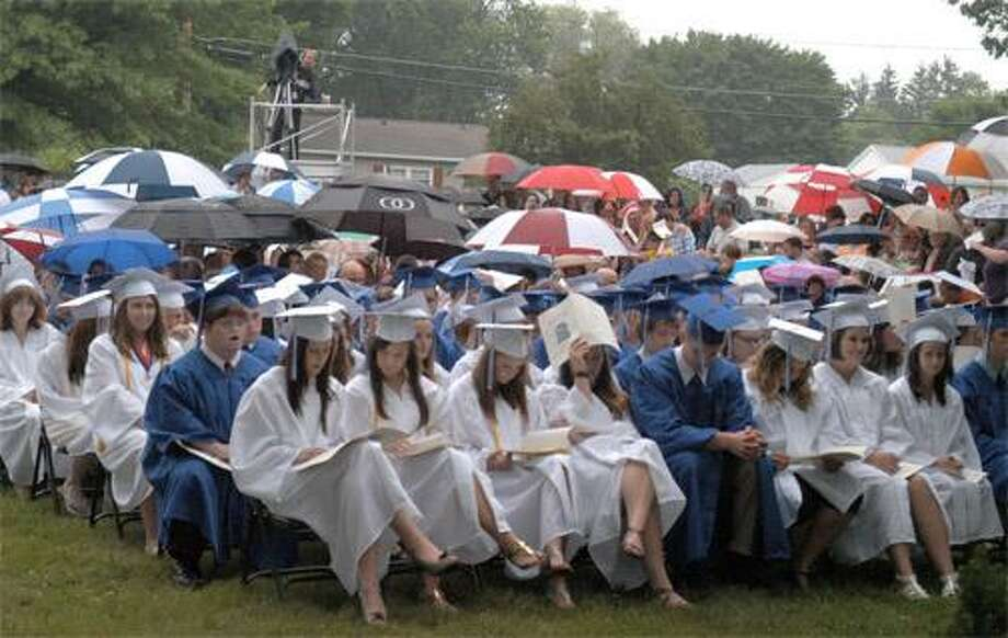 Family and friends open umbrellas as a light rain begins to fall during the second half of ceremonies at Oneida High School's 2011 commencement exercises on the front lawn of the school Saturday morning. Dispatch Photo by KURT WANFRIED