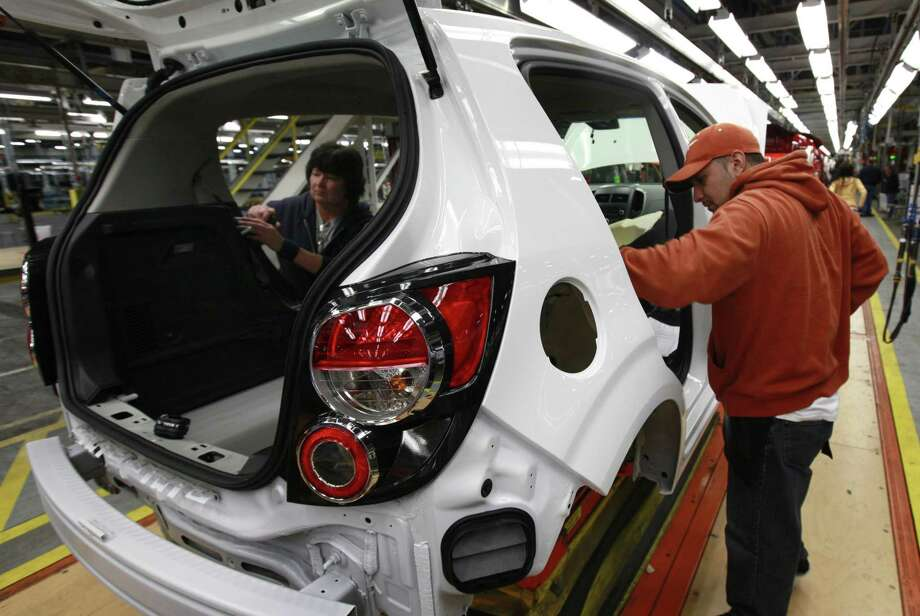 In this May 19 photo, line workers assemble a pre-production Chevrolet Sonic at the General Motors Orion Assembly plant in Orion Township, Mich. Businesses boosted their orders for machinery, electronics products and airplanes in May after a big cutback in the previous month. (AP Photo/Paul Sancya) Photo: AP / AP