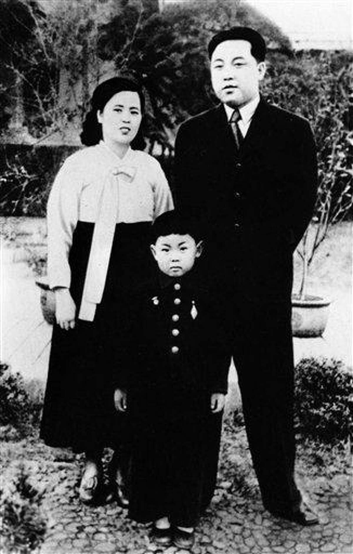 In this undated photo from North Korea's official Korean Central News Agency, distributed by Korea News Service, Kim Jong II, center, takes part in a souvenir picture during his childhood with his parents, North Korean leader Kim Jong Suk, right, and leader Kim Il Sung. North Korea's news agency reported today that Kim Jong Il had died on Saturday, Dec. 17 after having a heart attack on a train. He was 69. Associated Press