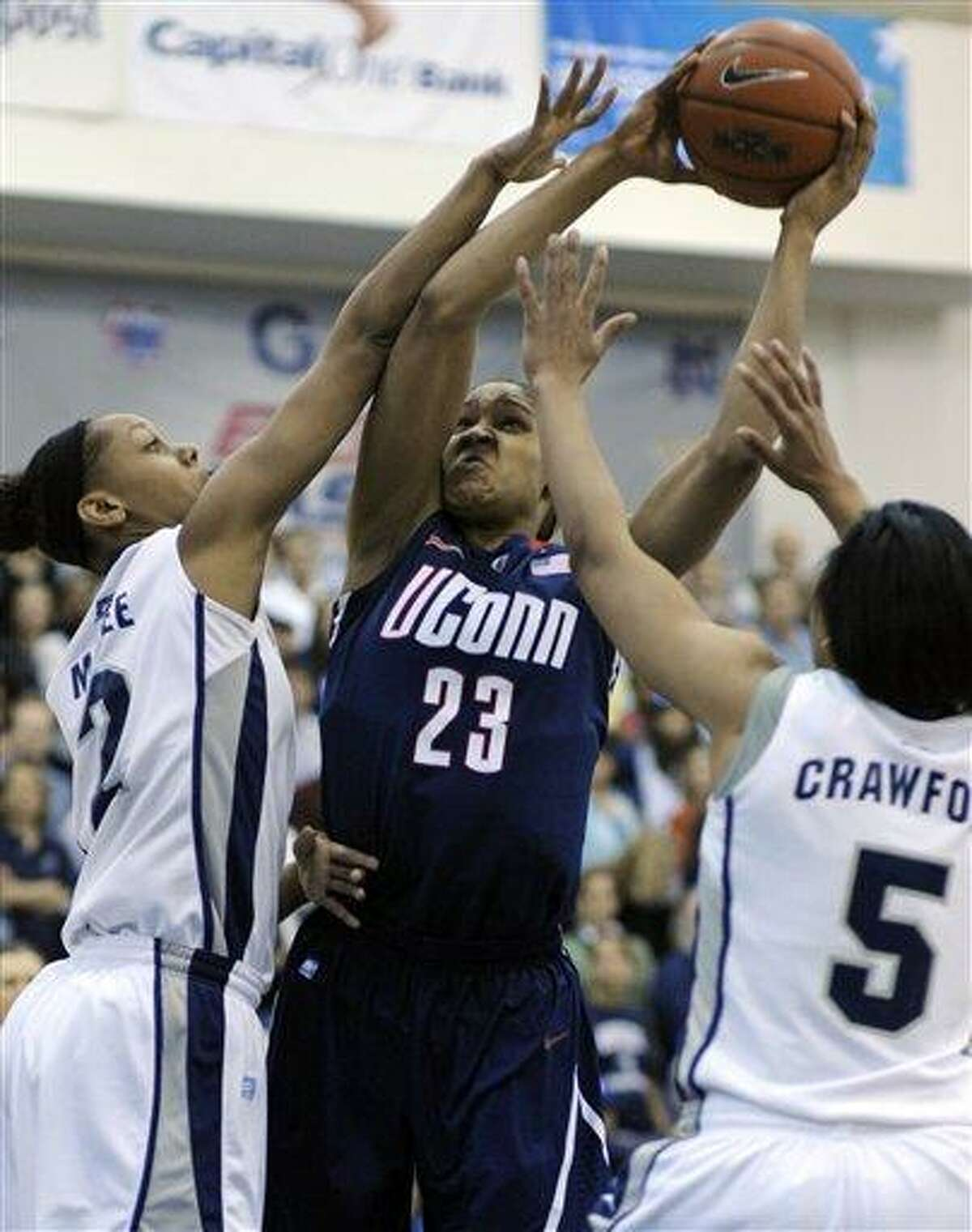 Connecticut forward Maya Moore, 23, center, is tied-up by Georgetown forwards Tia Magee, 2, left, and Adria Crawford during the first period of their Big East game in Washington, Saturday, Feb. 26, 2011. (AP Photo/Cliff Owen)