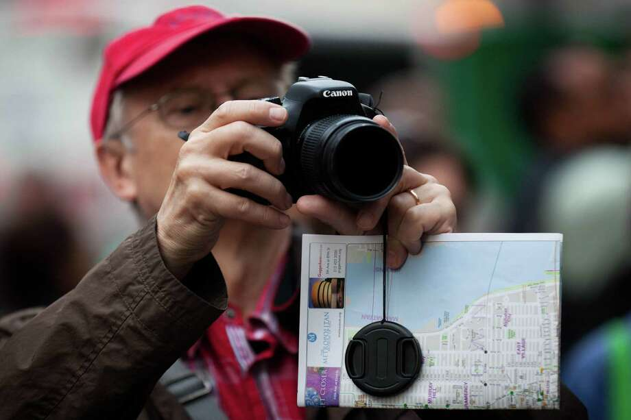 In this photo taken Tuesday,a spectator takes a photograph of the festivities at the Occupy Wall Street protests in Zuccotti Park, in New York. (AP Photo/John Minchillo) Photo: ASSOCIATED PRESS / AP2011