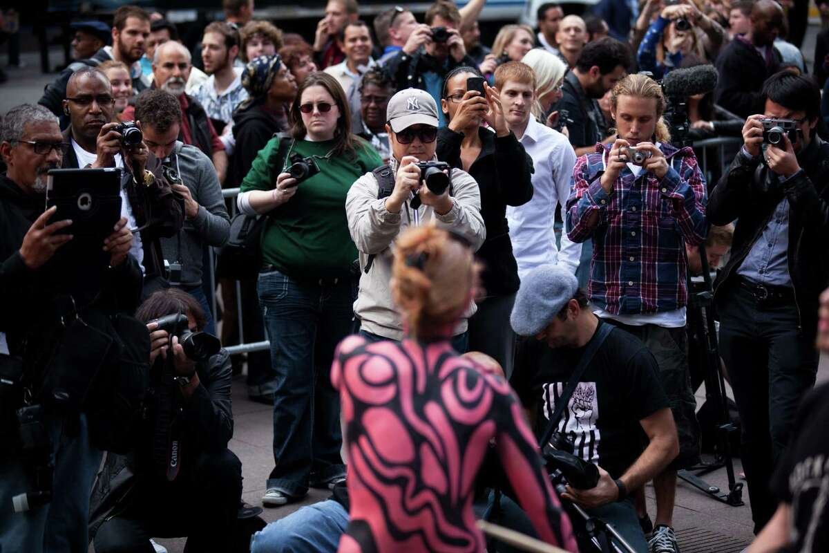 In this photo taken Tuesday, spectators swarm the Occupy Wall Street protests with their cameras in Zuccotti Park in New York. The protests against corporate greed and various issues have continued for more than a month and spawned similar uprisings around the world, attracting participants and tourists from around the country and beyond. (AP Photo/John Minchillo)