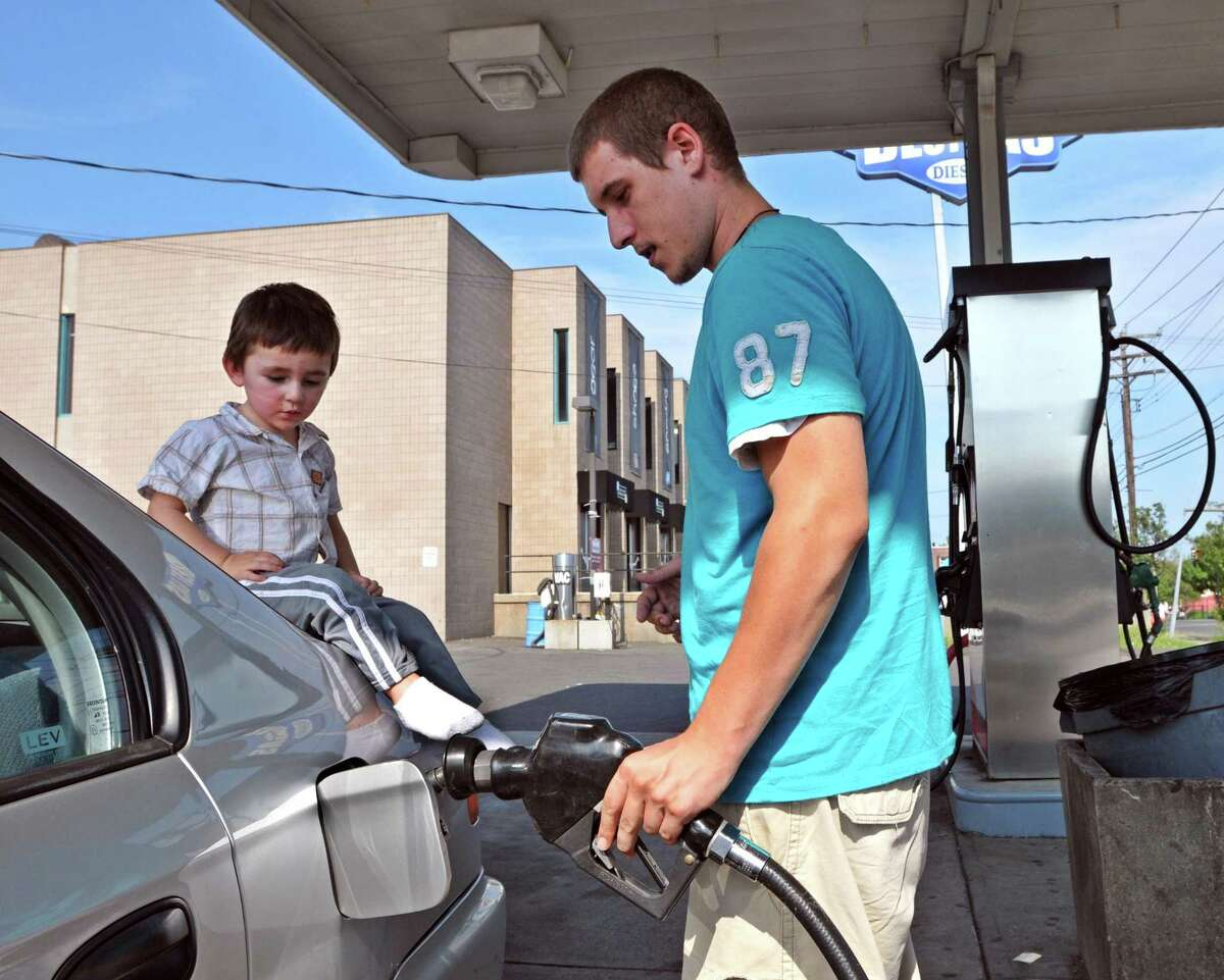 Justin Otto fills up at Best Gas in West Haven with a friend, Joseph Michael Thomas. Gas prices contributed to a rise in consumer spending last month. (Photo by Peter Casolino/New Haven Register)