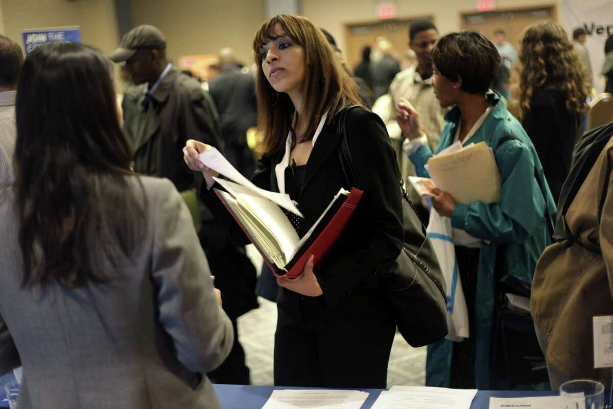 In this April 18 photo, job seekers talk to employers at a job fair in New York. Fewer people applied for unemployment benefits last week, partly reversing a sharp jump in applications the previous week. (AP Photo/Seth Wenig)