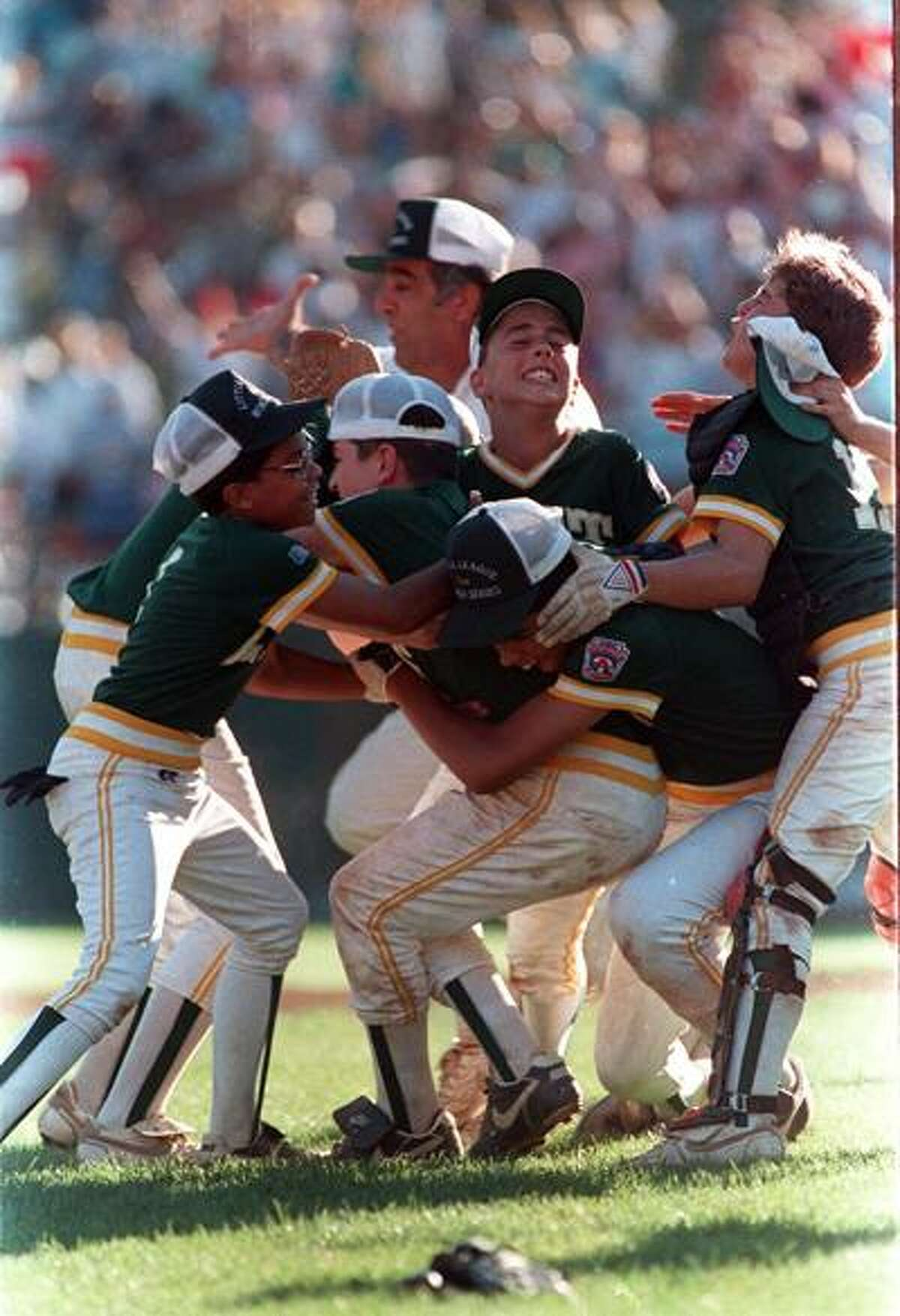 Members of the Trumbull,Conn., Little League team mob winning pitcher Chris Drury, second from left with cap askew, Aug. 26, 1989 as they celebrate on the field at Williamsport, Pa. Connecticut had just defeated Taiwan in the championship game of the Little League World Series. In background is Connecticut coach Bob Zullo. (AP Photo/Rusty Kennedy)