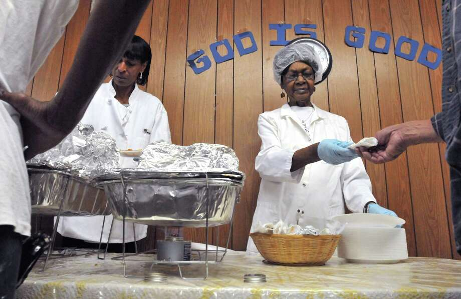 """New Haven--Volunteers Alonda Via, left, and Gloria Vaughn serve food at the Thomas Chapel Church of Christ Daily Bread Kitchen Wednesday.  The Food Research and Action Center has released its """"Food Hardship in America"""" report.  Photo by Brad Horrigan/New Haven Register-08.17.11."""