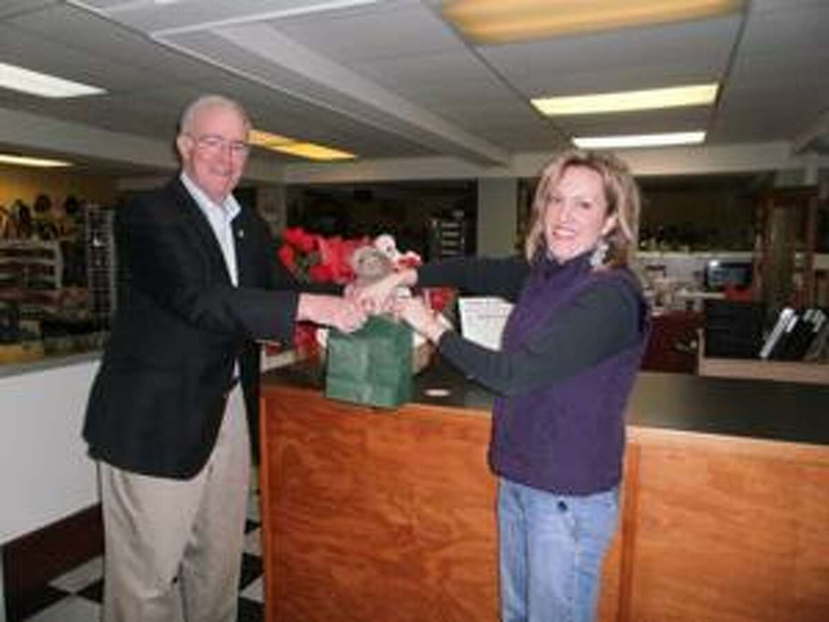 """SUBMITTED PHOTO Oneida Chamber of Commerce Executive Vice President John Reinhardt left and Oneida Commons Vendor Andrea Hitchings draw the names of the winners of the """"Wine & Dine Your Valentine"""" event."""