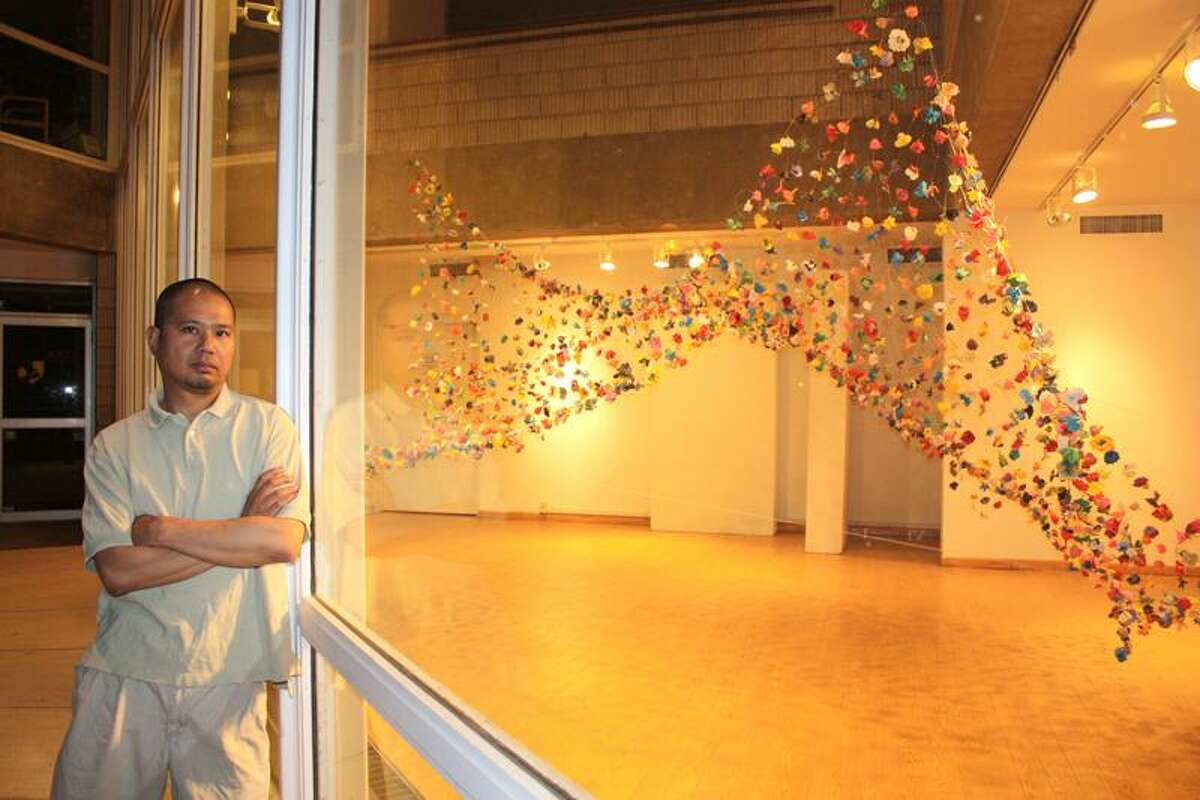 """Noel Sardalla: Artist Noel Sardalla of New Haven poses in front of his """"here/there/everywhere"""" at Creative Arts Workshop's Hilles Gallery."""