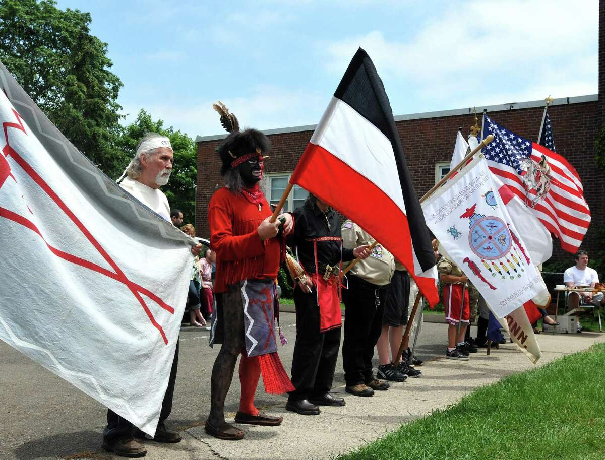 Native Americans and Boy Scouts hold flags at a ceremony in East Haven. Peter Casolino/Register