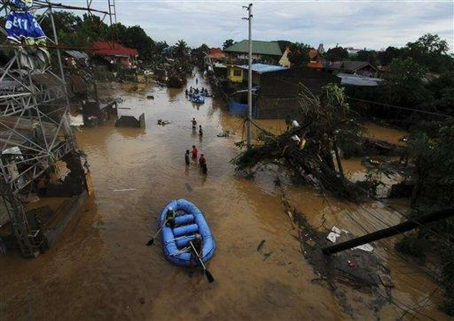 Rescuers paddle their rubber boat to search for survivors following a flash flood that inundated Cagayan de Oro city, Philippines, Saturday, Dec. 17, 2011. A tropical storm triggered flash floods in the southern Philippines, killing scores of people and missing more. Mayor Lawrence Cruz of nearby Iligan said the coast guard and other rescuers were scouring the waters off his coastal city for survivors or bodies that may have been swept to the sea by a swollen river. (AP Photo/Froilan Gallardo) Photo: ASSOCIATED PRESS / AP2011