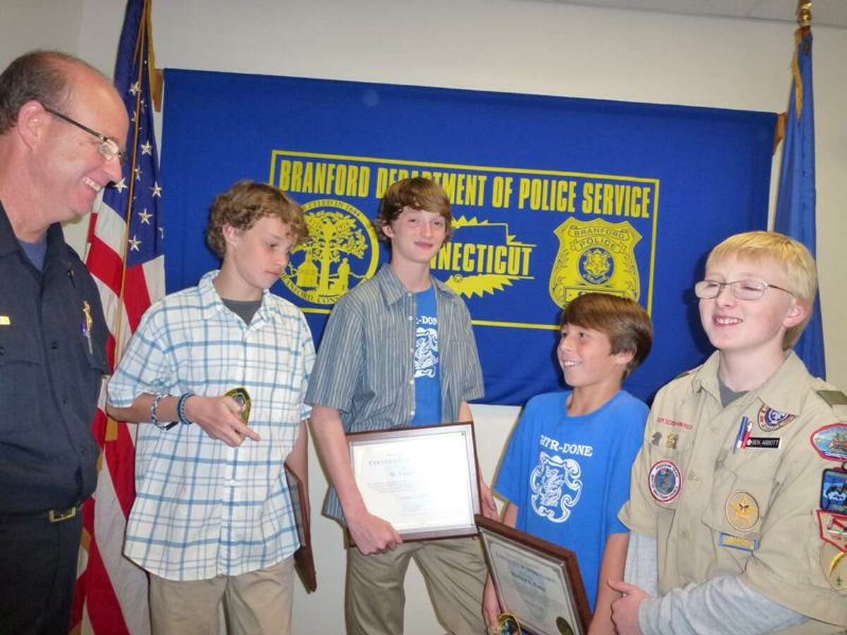 Branford Police Chief Kevin Halloran honors Boy Scouts Conor Duffy, 14; Eamon Duffy, 13; Ben Abbott, 14; and Matt Potter, 11, for their civic help during Hurricane Irene.
