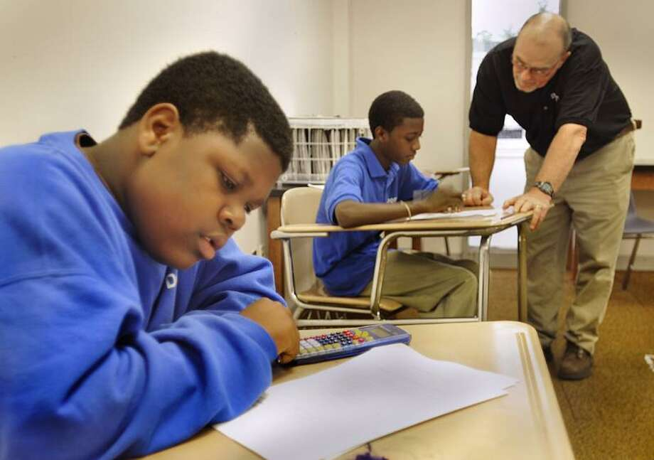 Damien Smith (front) and  Maurice Richardson work on final exams at Domus Academy. Answering a question for Richardson is principal Michael McGuire.