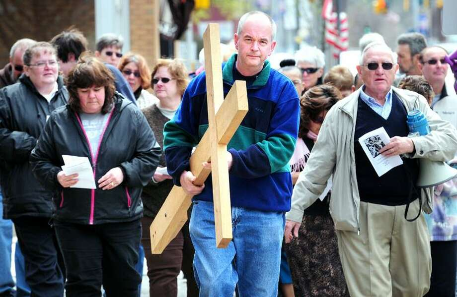 Rich Zdrowski, center, of Derby carries the cross up Main Street in Ansonia during the Way of the Cross procession for Good Friday. Arnold Gold/Register