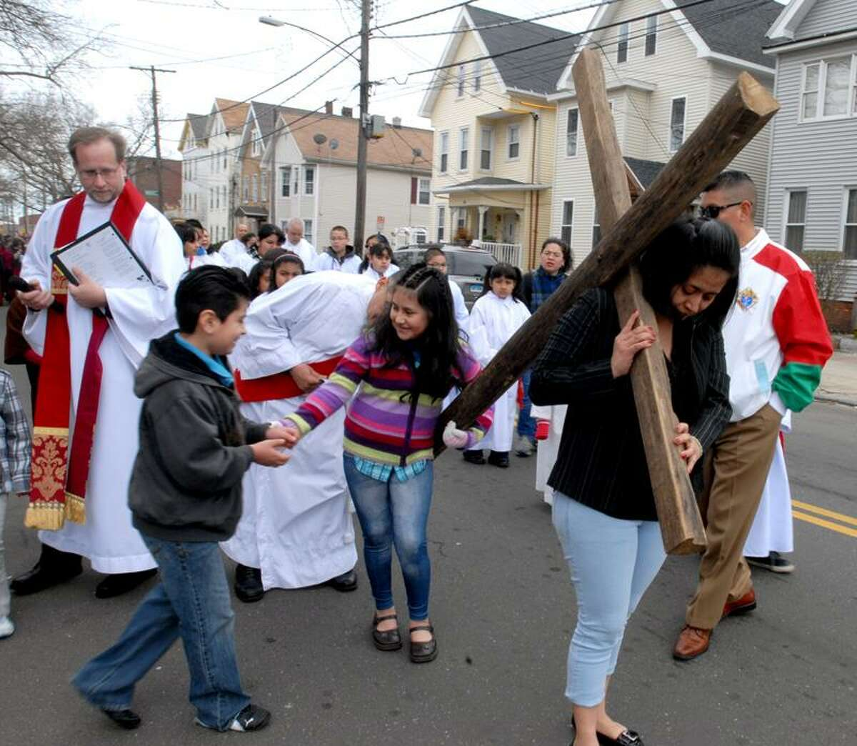 Carolina Paredes, parishioner of St.Rose of Lima Church in New Haven, leads the traditional Way of the Cross procession on Blatchley Avenue Friday. Her daughter, Oyuky, passes her end of the cross on to her brother, Alexander, as they assist their mother. Caroline Kowalczyk/Register