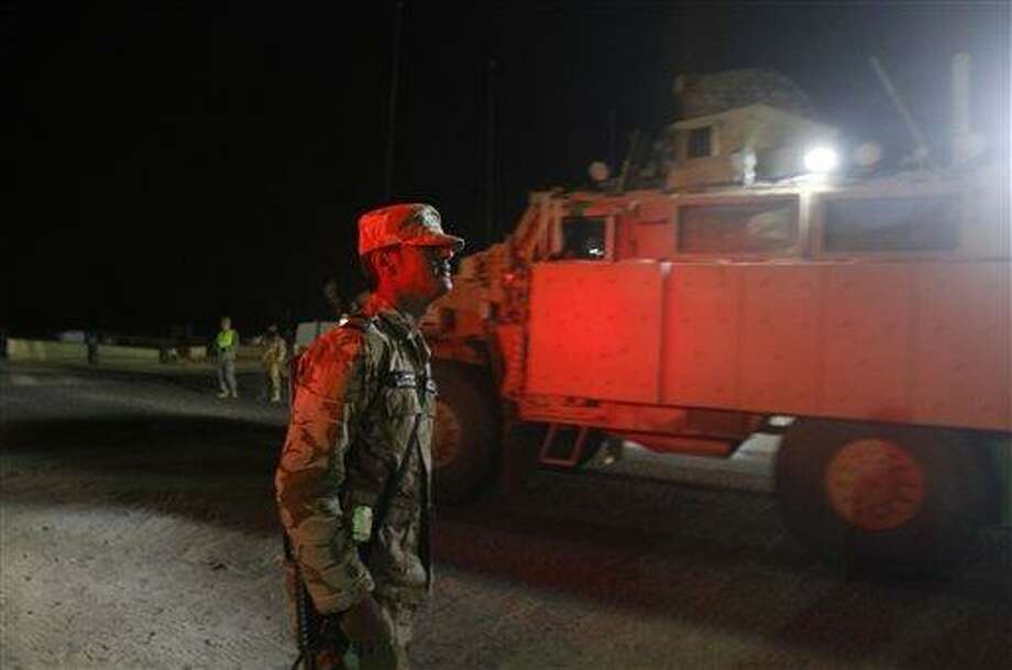 A Kuwaiti border guard watches a convoy from the U.S. Army's 3rd Brigade, 1st Cavalry Division crossing the border from Iraq into Kuwait, Sunday, Dec. 18, 2011. The brigade's special troops battalion are the last American soldiers to leave Iraq. The U.S. military says the last American troops have left Iraq as the nearly nine-year war ends. (AP Photo/Maya Alleruzzo) Photo: AP / Maya Alleruzzo/The Associated Press