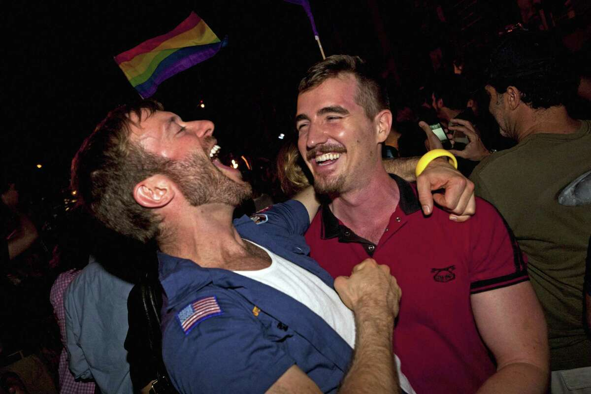 Colin Cunliffe, left, and Brewter Mccall, right, of Manhattan, celebrate the legalization of same-sex marriage in New York State outside the Stonewall Inn on Christopher St, Friday, June 24, 2011, in New York. The measure passed, 33-29, following weeks of tense delays and debate. (AP Photo/John Minchillo)