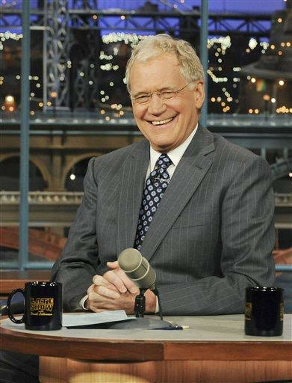 """FILE - In this April 21, 2010 file photo released by CBS, host David Letterman is shown on the set of the """"Late Show with David Letterman, in New York. A frequent poster on a jihadist website has threatened David Letterman, urging Muslim followers to """"cut the tongue"""" of the late-night host because of a joke made by the comic on his late-night CBS show. The poster, who identified himself as Umar al-Basrawi, was reacting to something Letterman said after the U.S. military said on June 5 that a drone strike in Pakistan had killed al Qaida leader Ilyas Kashmiri. (AP Photo/CBS, Heather Wines)"""