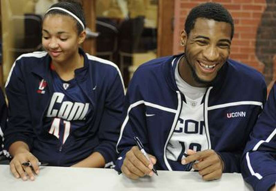 Connecticut freshmen Kiah Stokes, left, and Andre Drummond, right, share a light moment at a men's and women's basketball team autograph session during First Night NCAA college basketball exhibition, in Storrs, Conn., Friday, Oct. 14, 2011.  (AP Photo/Jessica Hill) Photo: AP / AP2011