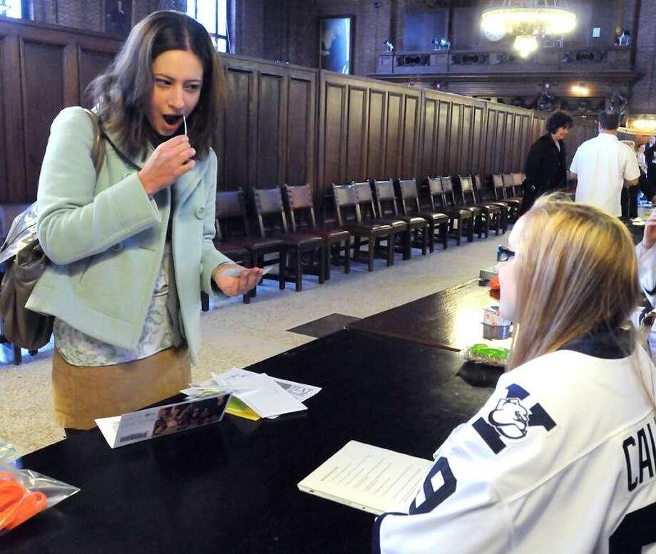 Yale University senior Elena Hoffnagle, left, swabs her cheek during Thursday's bone marrow donor drive at the university in New Haven. At right is Yale hockey player Erin Callahan. Mara Lavitt/Register
