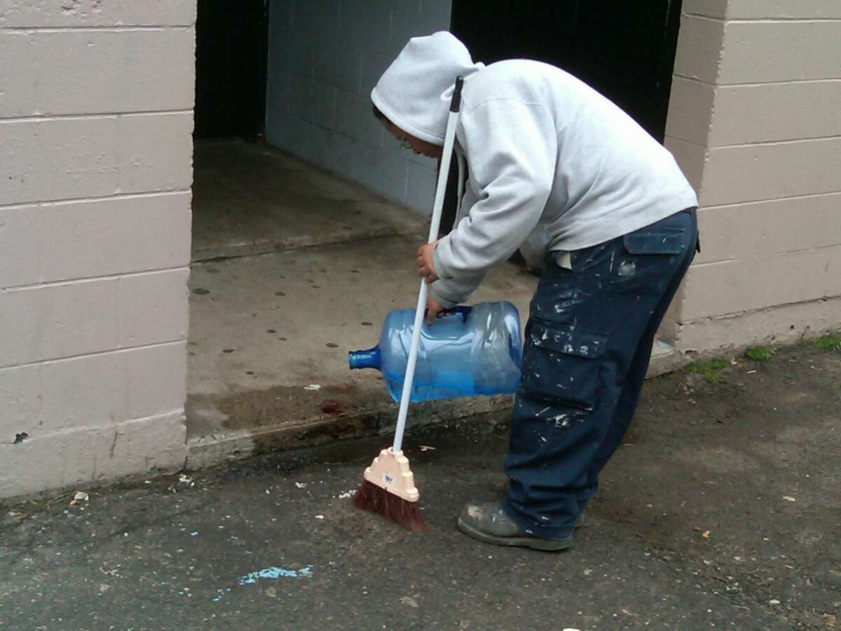 John Rivera, a maintenance worker at Church Street South, cleans blood from the stoop at the homicide scene there. William Kaempffer/Register