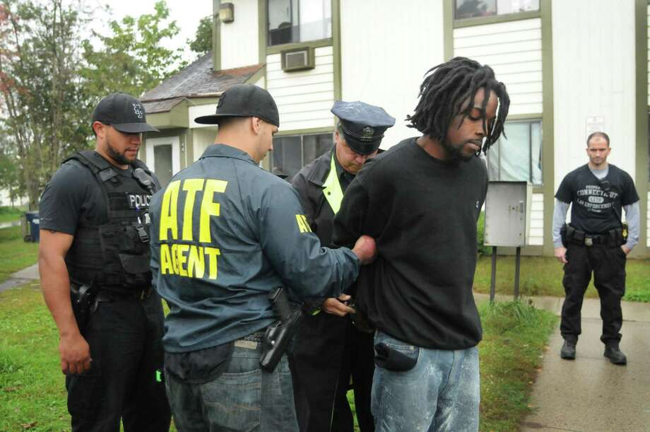 Police and ATF agents look on as ATF agent Dave Zannelli holds Abdualli Blake as he's handcuffed and arrested for multiple firearms violations Wednesday on Division Street in New Haven. Raids were being conducted across the city Wednesday. (Melanie Stengel/Register)