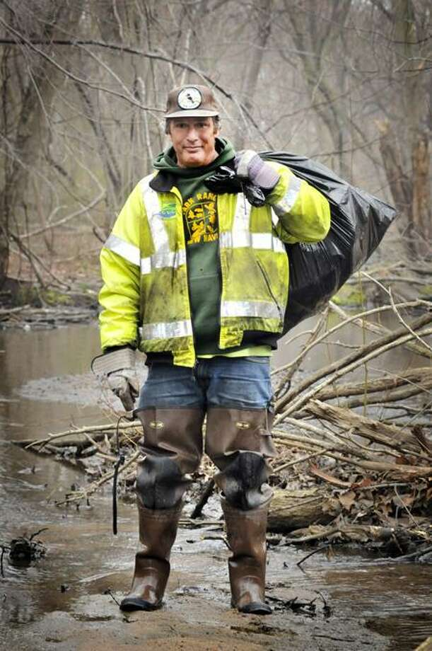 New Haven River Keeper, Peter Davis, stands in Beaver Creek with one bag of the trash that he collected. Davis is being honored by CFE/save the Sound for his work in removing thash from New Haven's waterways. (Melanie Stengel/Register)