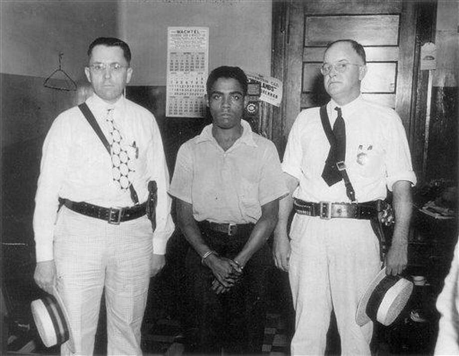 In this Friday, Aug. 14, 1936 picture, Rainey Bethea is photographed with Sheriff's Deputies Albert Riesz and Lawrence Dishman as they leave the Jefferson County jail in Louisville, Ky. for his execution in Owensboro, Ky. Bethea, a 22-year-old black man convicted of murdering and robbing a 70-year-old white woman, was the last person killed in a public execution in the United States. (AP Photo/Owensboro Messenger-Inquirer) Photo: AP / The Messenger-Inquirer