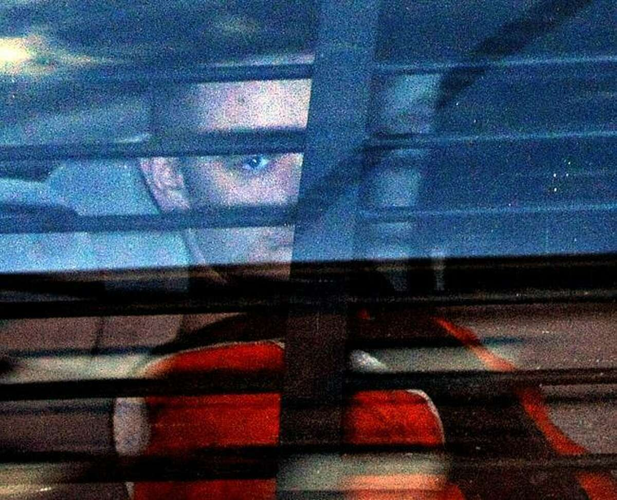 Riding in the rear of a police vehicle, Joshua Komisarjevsky leaves court Oct. 3. Peter Casolino/Register