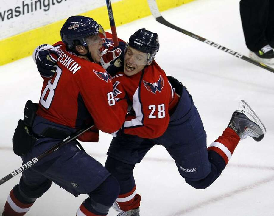 The Capitals' Alexander Semin (28) and Alex Ovechkin (8) celebrate Ovechkin's tying goal in the third period of Game 1 of a first-round playoff series with the New York Rangers on Wednesday in Washington. Semin scored the winner in overtime. (AP Photo/Alex Brandon) Photo: AP / AP2011